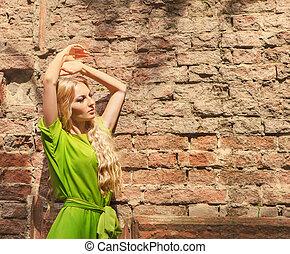 Beautiful blond woman in long green dress