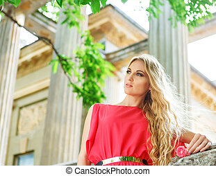 Beautiful blond woman in long red dress