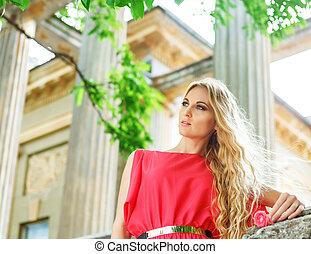 Beautiful blond woman in long red dress
