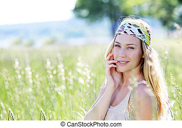 Beautiful blond woman in meadow with modern look