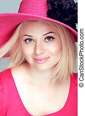 Beautiful blond woman in pink hat with makeup, smiling girl posing at studio