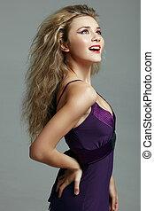 beautiful blond woman in purple dress.
