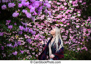 Beautiful blond woman in rhododendron garden.