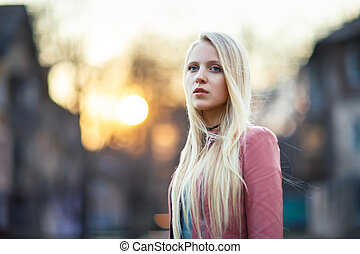 Beautiful blond woman in the street on sunset
