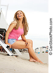 Beautiful blond woman laughing at the beach