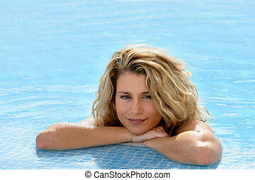 Beautiful blond woman leaning on the poolside