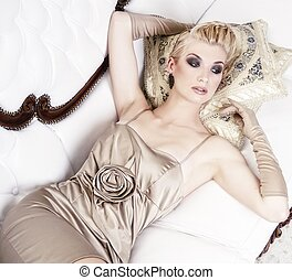 Beautiful blond woman lying on luxury sofa