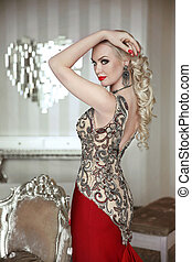 beautiful blond woman model posing in elegant dress with makeup and hairstyle at modern interior. indoor portrait.