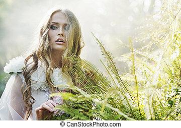 Beautiful blond woman next to the fern