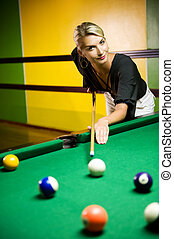 Beautiful blond woman playing billiards
