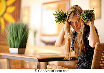 Beautiful blond woman playing with small pots of healthy green grass in spa.