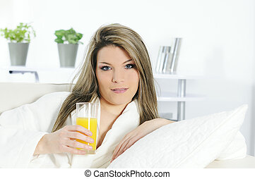Beautiful blond woman relaxing at home whith an orange juice