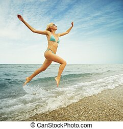 Beautiful blond woman running in the water
