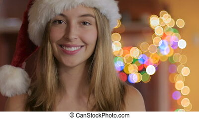 Beautiful blond woman smiles while wearing a Santa hat during Christmas