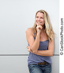Beautiful blond woman standing on grey background