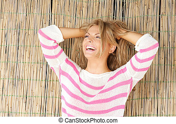 Beautiful blond woman standing outdoors laughing with hands in hair