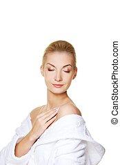 Beautiful blond woman touching her skin