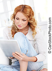 Beautiful blond woman using electronic tablet