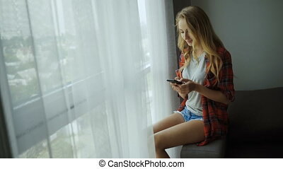 Beautiful blond woman using her phone at home.