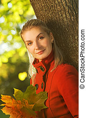 Beautiful blond woman with autumn leaves outdoors