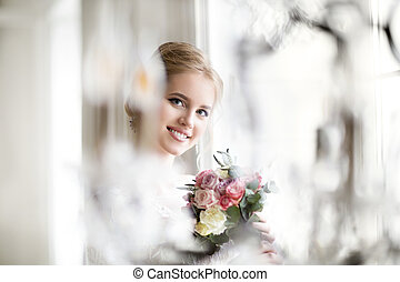 Beautiful blond woman with bouquet posing in a wedding dress