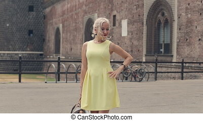 Beautiful blond woman with bright red lips posing next to the old castle in Milan
