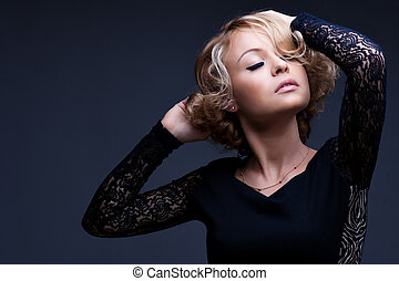 Beautiful blond woman with elegant black dress. Fashion photo