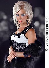 Beautiful blond woman with elegant black dress. Fashion photo on glitter background.
