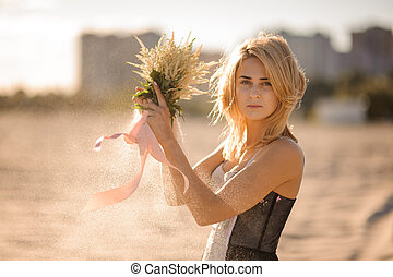 Beautiful blond woman with flowers in hands