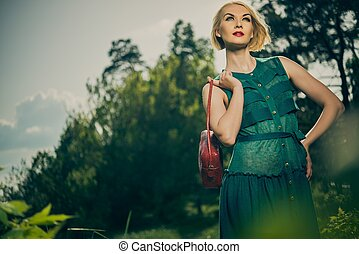 Beautiful blond woman with red bag in green dress outdoors
