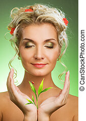 Beautiful blond woman with young plant. Isolated on white background