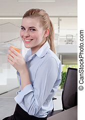 Beautiful Blond Young Businesswoman in Office with Coffee