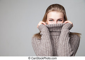 Beautiful blond young girl wears winter pullover over gray...