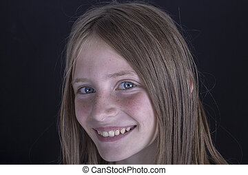 Beautiful blond young girl with freckles indoors on black background, closeup portrait