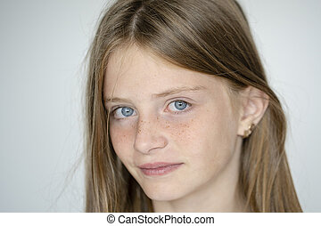 Beautiful blond young girl with freckles indoors on white wall background, closeup portrait