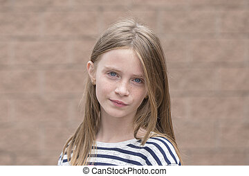 Beautiful blond young girl with freckles outdoors on wall background, closeup portrait