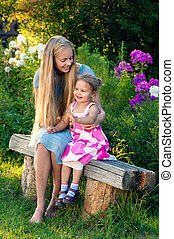 Beautiful blond young girl with her little sister in the countryside