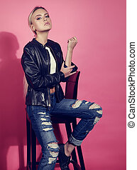 Beautiful blond young model posing in black leather jacket and blue ripped jeans on chair on pink background. Fashion portrait