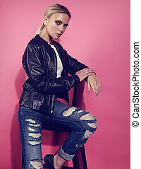 Beautiful blond young model posing in black leather jacket and blue ripped jeans on chair on pink background. Closeup portrait