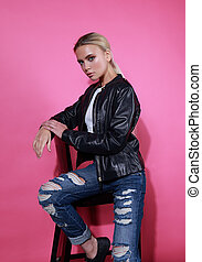 Beautiful blond young model posing in black leather jacket and blue ripped jeans on chair on pink background