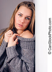 beautiful blond young woman looking at camera in knitwear