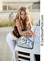 Beautiful blond young woman posing by headlight of white...