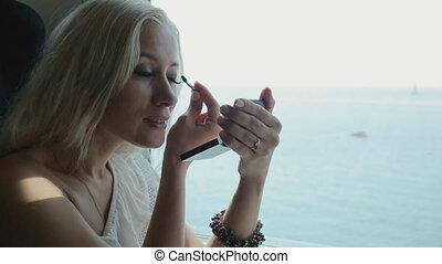 Beautiful blonde applying eye shadow and lip gloss sitting...