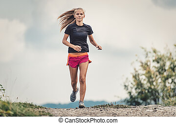 Beautiful blonde athlete runs on dirt road in the hills