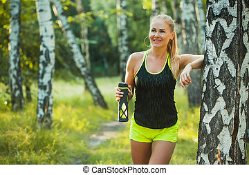 Beautiful blonde athletic woman on a run in the forest