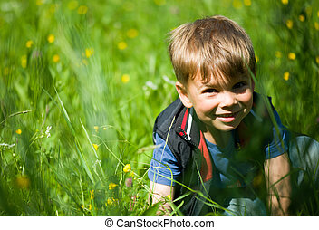 Beautiful blonde boy in the grass