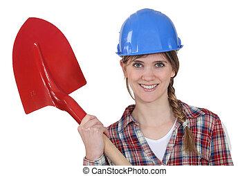 beautiful blonde bricklayer holding shovel
