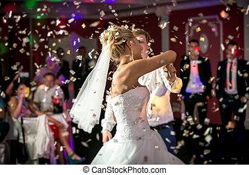 Beautiful blonde bride dancing at restaurant in flying confetti