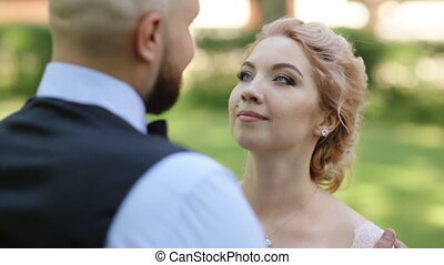 Beautiful blonde bride looks with a smile at her groom over his shoulder