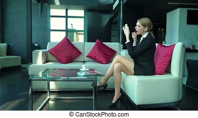 Beautiful blonde business woman sits in the bar or cafe, paints her lips by pink lipstick, makes selfie, reads tablet, uses phone as mirror, drinks coffee. Sexy girl alone in restaurant, doing makeup